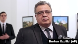 Russian Ambassador to Turkey Andrei Karlov moments before Mevlut Mert Altintas (background left) opened fire and killed him in Ankara on December 19, 2016