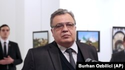 Andrei Karlov, the late Russian Ambassador to Turkey, at an exhibition in Ankara moments before he was shot dead by Mevlut Mert Altintas, who is visible in the background on the left. (file photo)