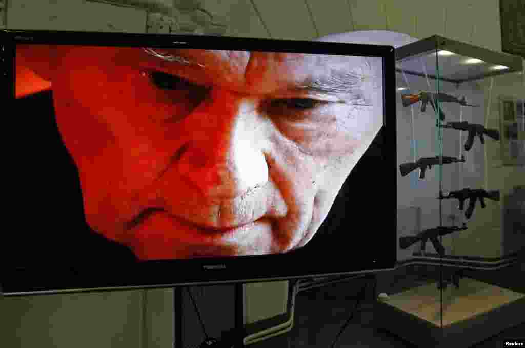 A portrait of Mikhail Kalashnikov is seen on a screen near a display of his weapons during an exhibition at the Artillery Museum in St. Petersburg, Russia. (Reuters/Alexander Demianchuk)