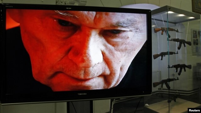 The image of AK-47 inventor Mikhail Kalashnikov is seen on a screen near a display of his weapons during an exhibition at the Artillery Museum in St. Petersburg.