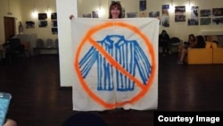Russian artist Yelizaveta Savolainen with the banner she used to protest against a lecture by a pro-Kremlin activist at the Russian State University for the Humanities.
