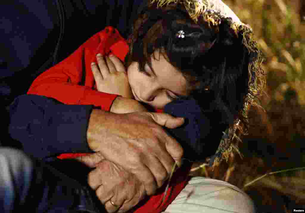 A young Syrian girl sleeps in the arms of a relative after her family was after apprehended by Serbian border police. Most illegal migrants see Serbia as the gateway to Hungary and the borderless Schengen zone.