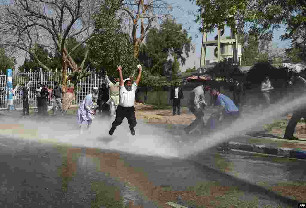 Pakistani employees of Pakistan International Airlines shout slogans as police use a water cannon on them during a protest near Karachi International Airport on February 2. (AFP/Rizwan Tabassum)