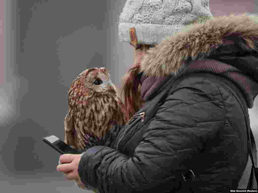 A woman with an owl, which poses for pictures with tourists, uses her cell phone as she waits for custom in central Kyiv, Ukraine. (Reuters/Gleb Garanich)