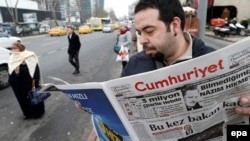 Мужчина читает газету Cumhuriyet. Иллюстративное фото.