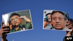 A supporter of former military ruler Pervez Musharraf holds up posters bearing his image during a rally in Islamabad on January 15.
