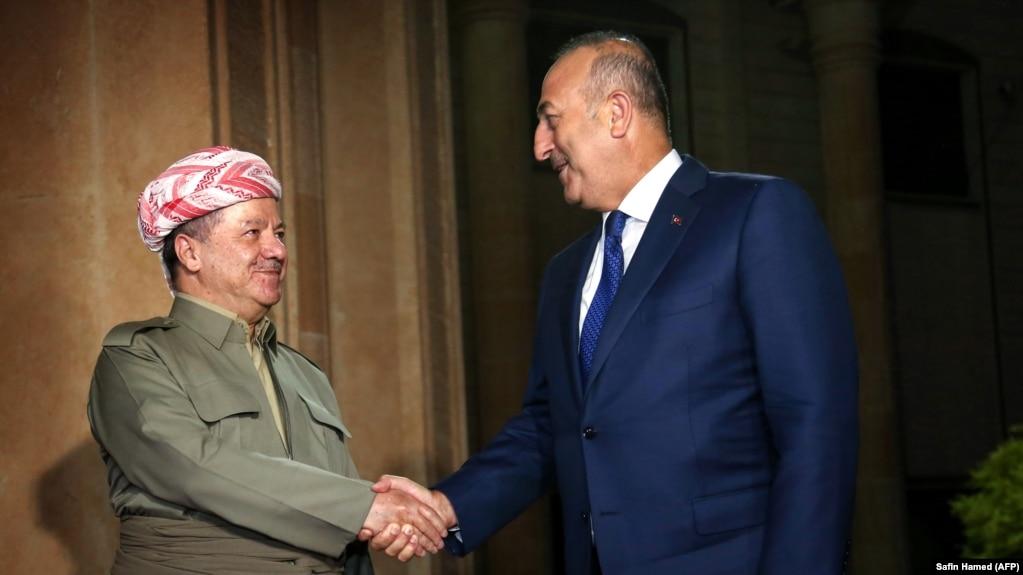 The president of Iraq's Kurdish autonomous region, Masud Barzani (left), meets with Turkish Foreign Minister Mevlut Cavusoglu in Irbil on August 23.
