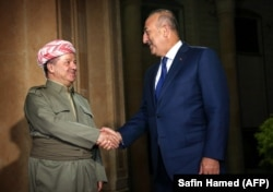 Iraq's Kurdistan region President Masud Barzani (left) meets with Turkish Foreign Minister Mevlut Cavusoglu in Irbil on August 23.