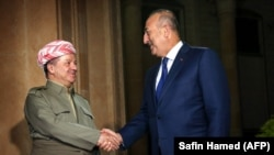 The president of Iraq's Kurdish autonomous region, Masud Barzani (left), meets with Turkish Foreign Minister Mevlut Cavusoglu in Irbil on August 23.