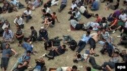 Ethnic Uzbek men rest at a refugee camp on the Kyrgyz side of the border with Uzbekistan on June 20.