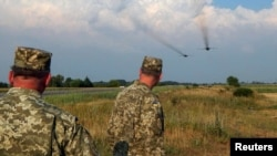 Ukrainian servicemen watch Sukhoi Su-24 front-line bombers fly during military aviation drills as Russia accuses Ukraine in incursion into annexed Crimea, in Rivne region, August 10, 2016