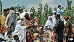 Flood survivors speak with security personnel as they wait for their turn to board army boats while they are evacuated from the flood-hit Chakdarra area of Swat on August 4.