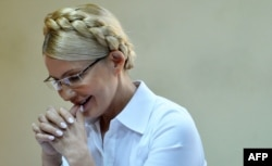 Yulia Tymoshenko smiles as she listens to the judge in Kyiv's district court during her trial on July 15, 2011.