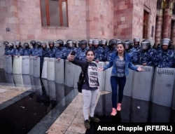 Passersby take selfies in front of riot police guarding the government building in Yerevan's Republic Square on the evening of April 19.