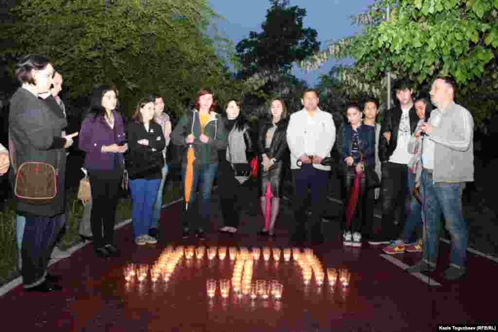 Представители крымскотатарской диаспоры зажгли свечи и расставили их на аллее депортированных народов в Центральном парке отдыха в Алматы в форме тамги - национальной символики крымских татар.