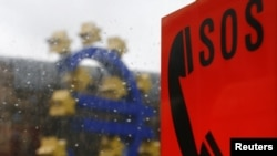 A sculpture of the euro's logo is seen behind an emergency telephone in Frankfurt.