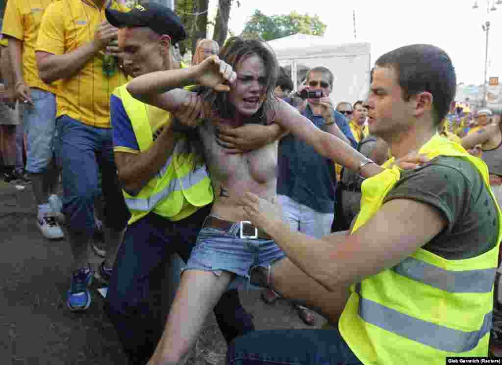 Охоронці затримують Оксану Шачко під час акції протесту на «Євро-2012»