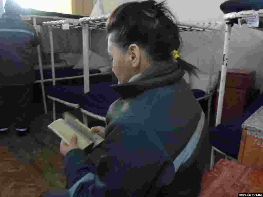 Женщина читает книгу в камере.