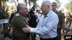 Israeli President Reuven Rivlin (R) is greeted by Israeli chief of Staff Gadi Eizenkot as he visits near the Israel-Gaza border area on August 23, 2016 (Photo by MENAHEM KAHANA / AFP)