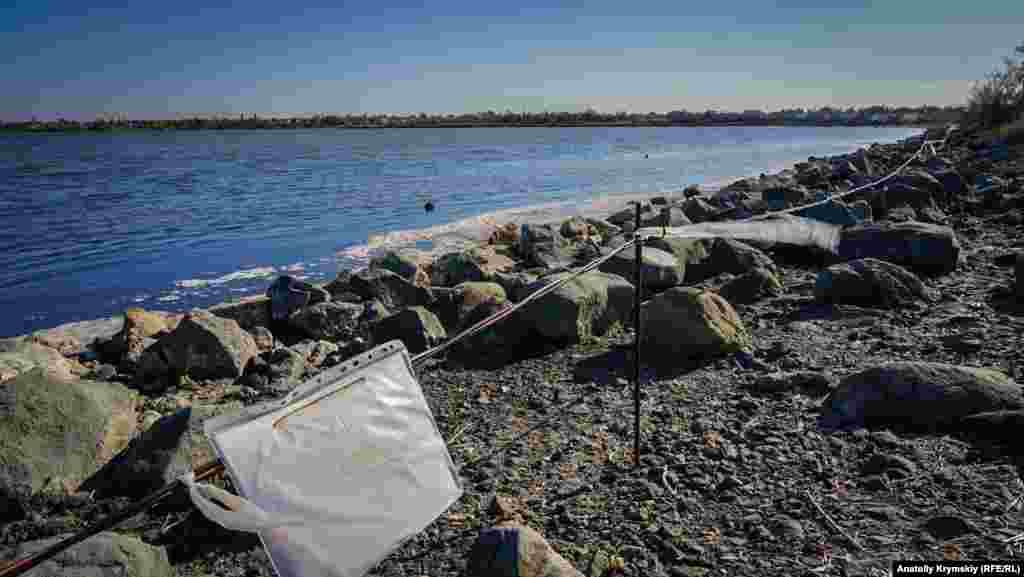Выцветшие бумажные листыв файле предупреждают о запрете купания в буферном бассейне озера