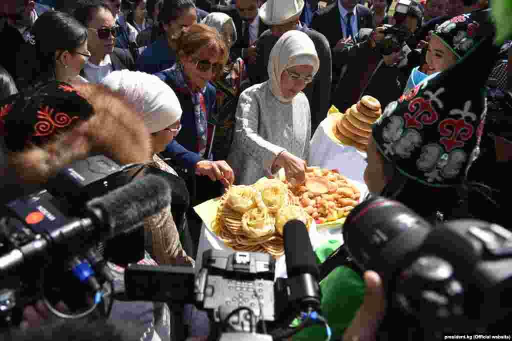 Түркиянын президенти Режеп Тайип Эрдогандын жубайы Эмине Эрдоган даам ооз тийип жатат.