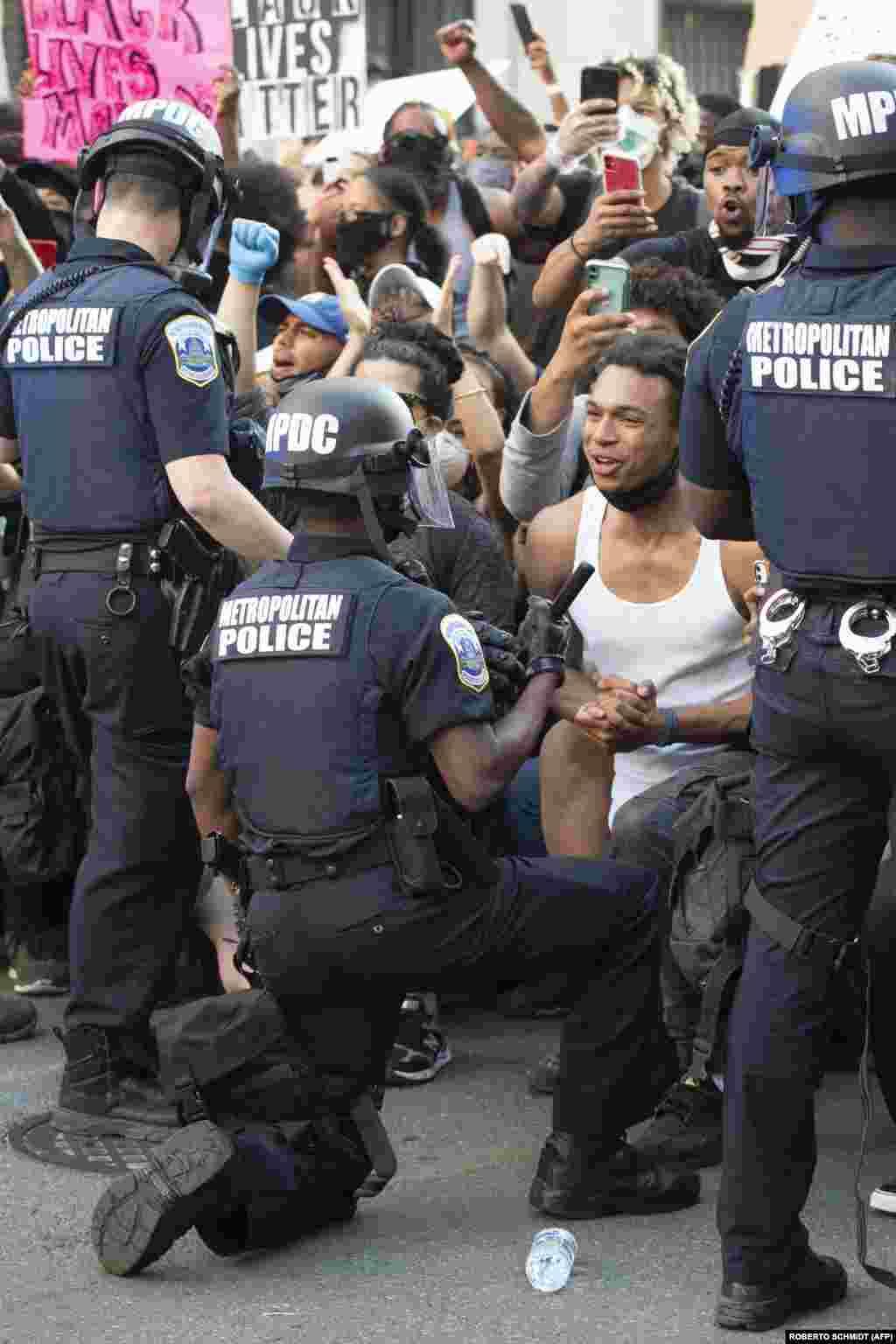 Еден човек вреска од емоции додека гледа како полицаец клечи, додека стотици протестираат против смртта на Џорџ Флојд веднаш до Белата куќа во Вашингтон.