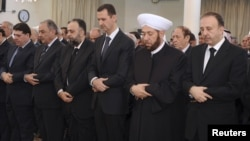 Башор Асад, раисиҷумҳури Сурия (нафари сеюм аз тарафи рост) дар ҳоли гузоштани намози Иди Қурбон