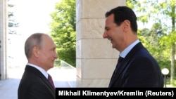Володимир Путін (л) вітає Башара Асада (п) під час зустрічі в Сочі, Росія