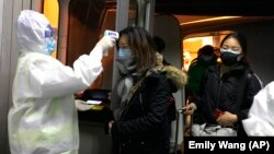 Медики перевіряють температуру в пасажирів, що прибули з Уханя, 22 січня 2020 року