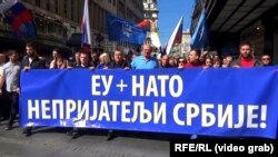 """Far-right protesters in Belgrade commemorate the NATO strikes in Serbia, walking behind a sign that reads """"EU + NATO, Our Enemies,"""" on March 24."""