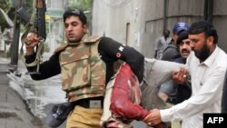 A Pakistani policeman carries the bloodied body of a worshiper at one of two mosques stormed by gunmen in Lahore.