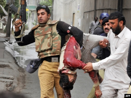 A police officer carries the body of a wounded worshiper at one of two mosques stormed by gunmen in Lahore on May 28.