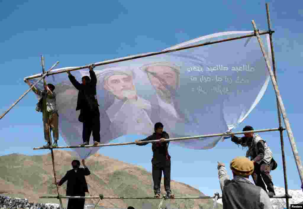 Supporters of Afghan presidential candidate Abdullah Abdullah hang up a banner before an election campaign in Panjshir Province. (Reuters/Ahmad Masood)