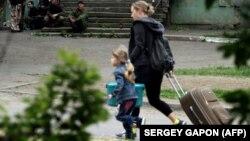 Жінка з дитиною тікає з кварталу, в якому триває бій між прикордонним підрозділом та проросійськими бойовиками, які штурмують частину, Луганськ, 2 червня 2014 року