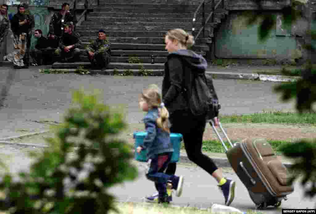 Женщина с ребенком уезжает из Луганска после того, как в одном из кварталов города началось вооруженное противостояние между сторонниками так называемой Луганской народной республики и подразделением украинских пограничников - 2 июня 2014