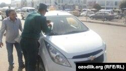 Инспектор по безопасности дорожного движения Андижана выписывает штраф водителю.