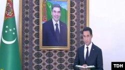 Serdar Berdimuhamedow prezident kakasynyň portretiniň öňünde prezidente hasabat berýär.