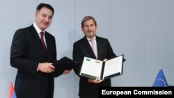 Armenian Economy Minister Karen Chshmaritian (left) with European Neighborhood Policy and Enlargement Negotiations Johannes Hahn in Brussels on November 3