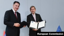 Belgium - EU Enlargement Commissioner Johannes Hahn (R) and Armenian Economy Minister Karen Chshmaritian sign a memorandum of understanding in Brussels, 3Nov2014.