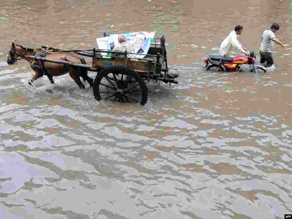 A Pakistani laborer directs his horse-drawn cart past pedestrians wading down a flooded street after heavy monsoon rain in Lahore on July 20.Photo by Arif Ali for AFP