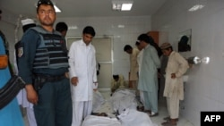 Police and civilians gather at a hospital morgue holding the bodies of suicide-bombing victims in Khost on June 20.