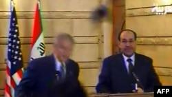 Президент США Джордж Буш уворачивается от ботинка, справа — иракский премьер-министр Нури аль-Малики. Ирак, 14 декабря 2008 года.