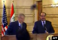 A screen shot shows U.S. President George W. Bush (left) ducking to avoid one of Zaidi's shoes.