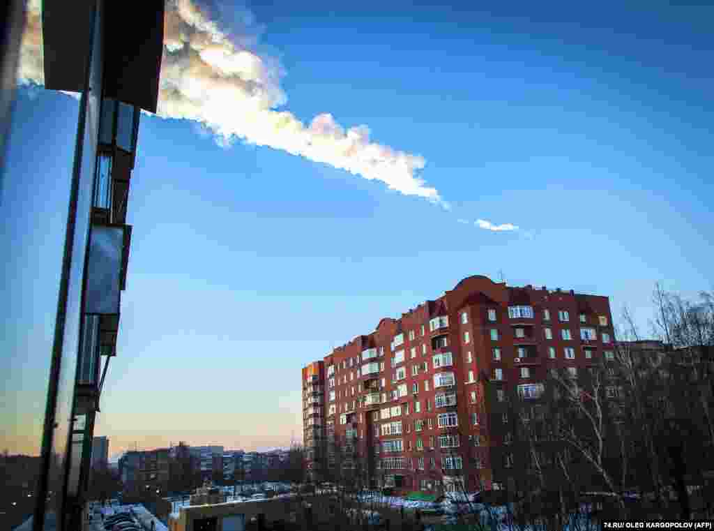 The trail of a meteor is seen above a residential apartment block in the Urals city of Chelyabinsk, Russia. The strike caused widespread injuries and damage. (AFP/Oleg Kargopolov)