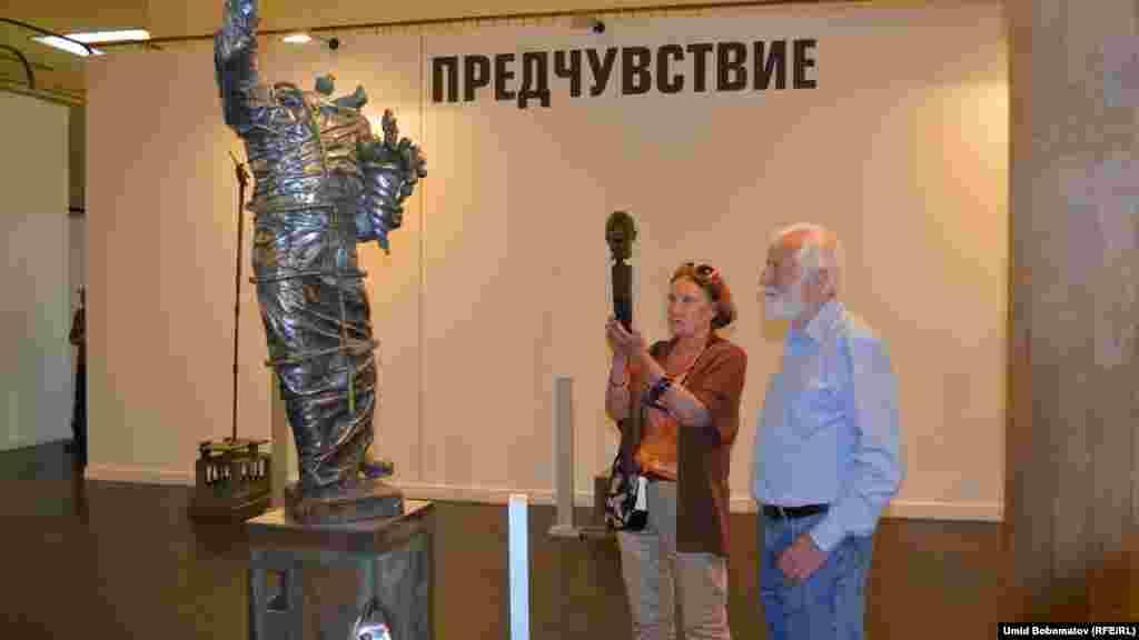 Қазақстандық мүсінші Еркін Мергеновтің көрмесіне қойылған мүсіндер мен оны тамашалап тұрған адамдар. Мәскеу, 16 шілде 2015 жыл.