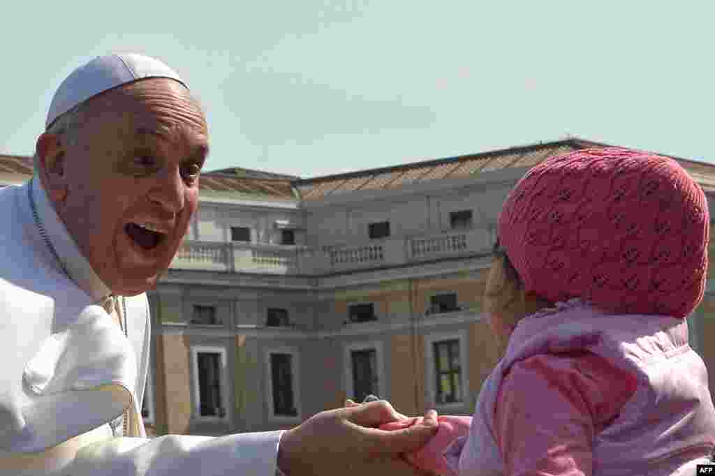 Pope Francis greets a young girl as he arrives for his weekly general audience at St. Peter's Square at the Vatican. (AFP/Alberto Pizzoli)