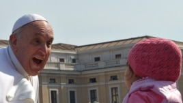 The pope greets a young girl outside the Vatican.