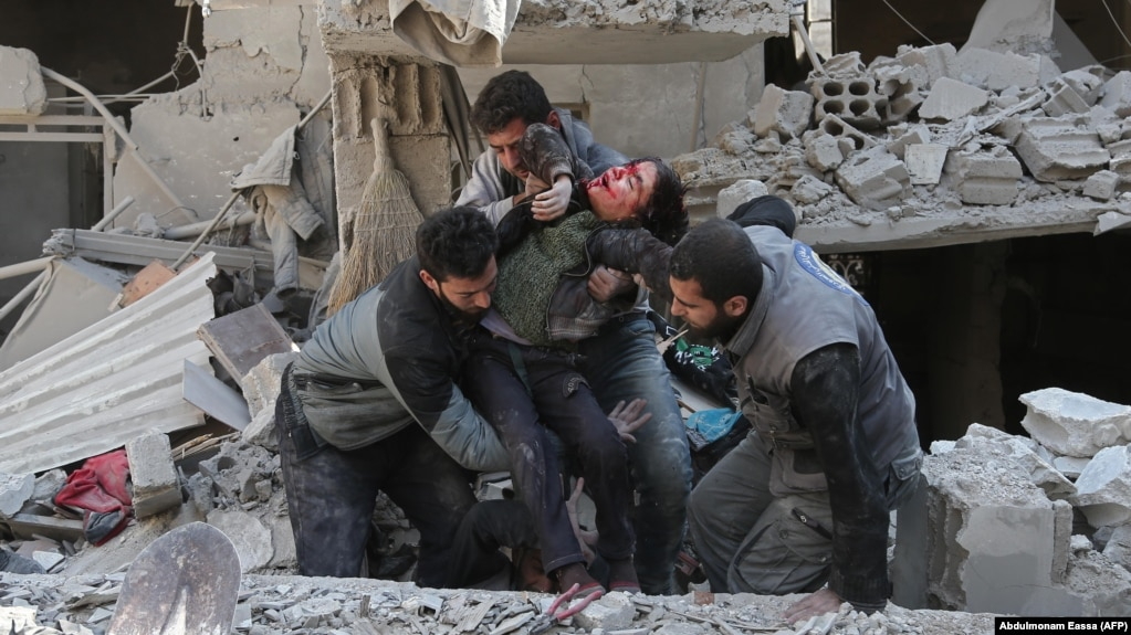 Emergency workers rescue a child following a reported regime air strike in the rebel-held Syrian town of Hamouria in the besieged Eastern Ghouta region on February 21.