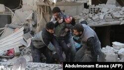 Сирийцы спасают ребенка после воздушного удара сил Асада в повстанческом городе Хамурия, в осажденном регионе Восточная Гута на окраине Дамаска, 21 февраля 2018 года.