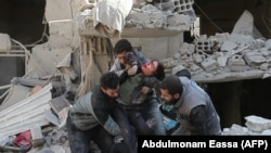 Сирийцы спасают ребенка после воздушного удара сил Асада в повстанческом городе Хамурия, в осажденном регионе Восточная Гута на окраине Дамаска. 21 февраля 2018 года.